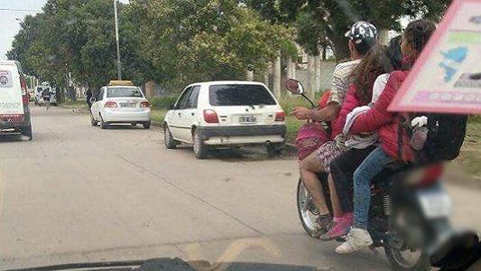 5 personas en una moto, todos sin casco y el cigarrillo al volante