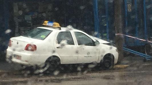 Entre la lluvia, un remis se estampó contra un cartel y un poste de luz
