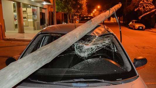 Viejo poste vencido por el viento daño severamente un auto