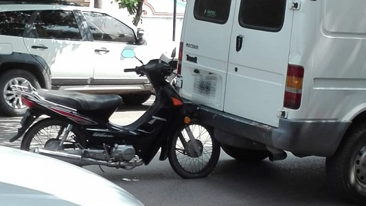 Moto quedó engancha de vehículo que dio para atrás y no la vio